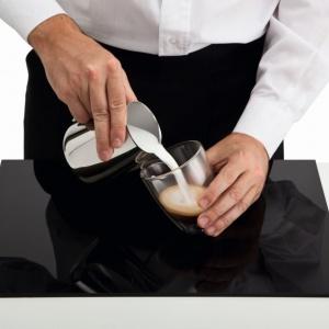 Serce - krok pierwszy. Zacznij nalewać mleczną piankę w samym środku espresso z wysokości około 6–7 cm od cremy, aby wydobyć ciemną barwę kawy.