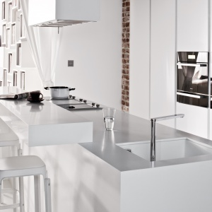 Minimalistyczna biała kuchnia, w której dominują proste linie i gładkie powierzchnie została ocieplona przez czerwoną cegłe na ścianie. Fot. Zajc Kuchnie, model Z4