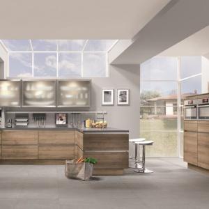 Poziomy rysunek drewna pięknie na frontach mebli kuchennych pięknie prezentuje się w zestawieniu z matową stalą i wieńczącym zabudowę szarym blatem. Fot. Nobilia
