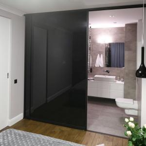 Granicę pomiędzy sypialnią i łazienkę wyznaczają czarne, szklane, półprzezroczyste drzwi. Projekt: Karolina Łuczyńska. Fot. Bartosz Jarosz