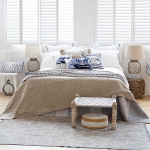 Granatowo-białe poduszki z nadrukami żaglówek w połączeniu z plecionymi meblami przywodzącymi na myśl plażowe kosze sprawiają, że w tej sypialni możemy poczuć się jak nad morzem. Fot. Zara Home