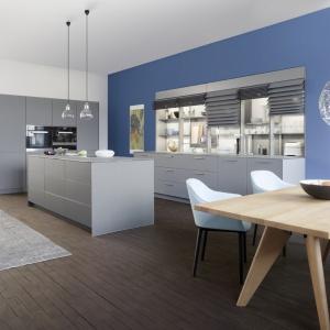 Nowoczesna kuchnia, w której meble w jasnoszarym kolorze stoją na tle niebieskiej ściany. Gładkie fronty wysokiej zabudowy i wyspy kuchennej są bezuchwytowe, podczas gdy zabudowa pod ścianą ma tradycyjne uchwyty oraz ciekawie otwierane fronty żaluzjowe (w górnej części). Fot. Leicht, model Classic-FS