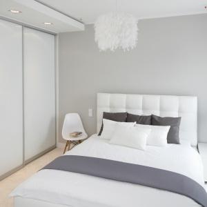 Ścianę za łóżkiem pomalowano szarą farbą, na tle której pięknie wyeksponowano biały tekstylny zagłówek. Projekt: Małgorzata Galewska. Fot. Bartosz Jarosz