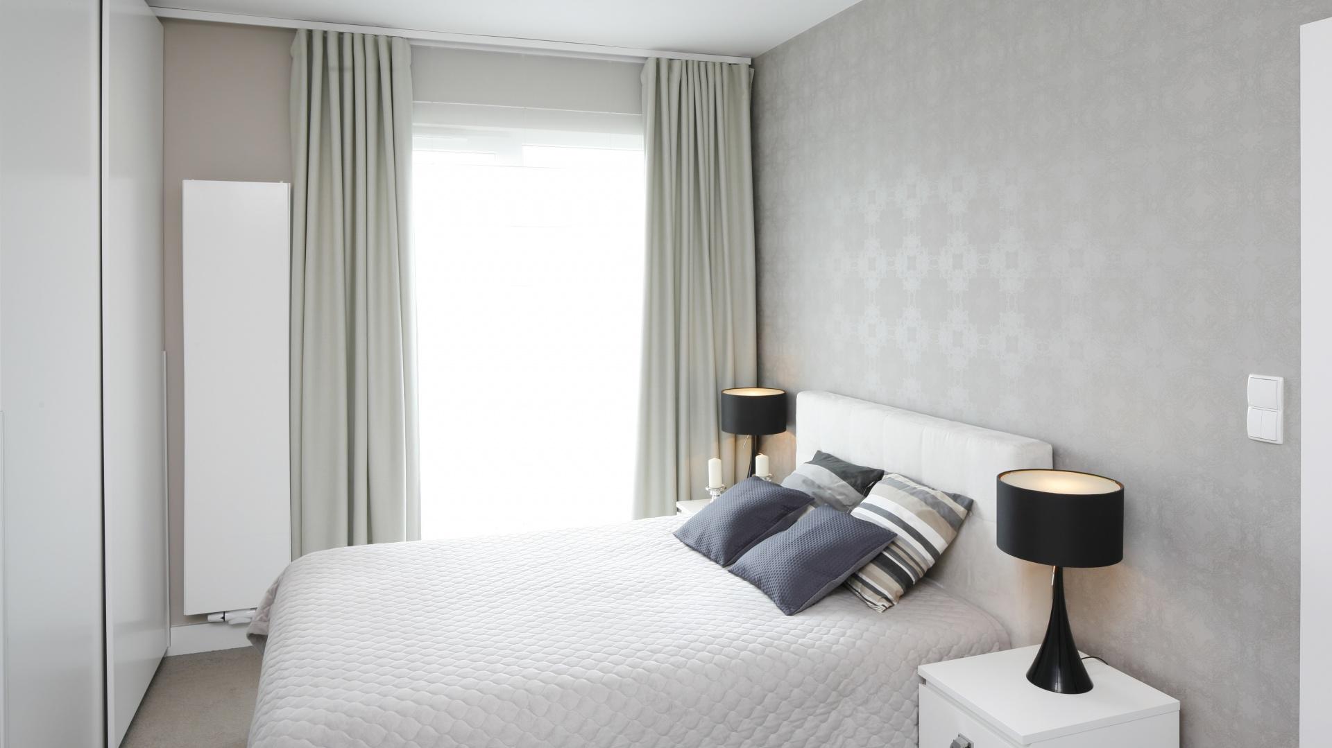 Jasne łóżko z tekstylnym zagłówkiem w kolorze ecru stanęło na tle ściany wykończonej piękną szarą tapetą z elegancki, bardzo subtelnym wzorem. Projekt: Małgorzata Galewska. Fot. Bartosz Jarosz