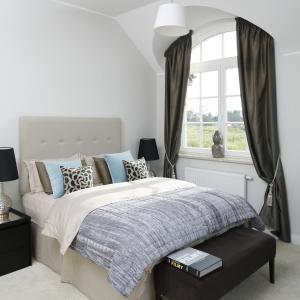 Białe ściany, miękka jasnoszara wykładzina na podłodze oraz tapicerowany zagłówek łóżka o podobnej barwie zostały zaakcentowane przez ciemniejsze akcenty w postaci podnóżka i zasłon w oknach. Projekt: Ventana. Fot. Bartosz Jarosz