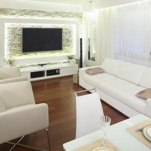 Białe meble wypoczynkowe oraz skrzyniowe w salonie harmonizują z jasnym kamieniem na ścianie za TV. Elementem ocieplającym wizualnie wnętrze jest drewniana podłoga. Projekt: Małgorzata Mazur. Fot Bartosz Jarosz