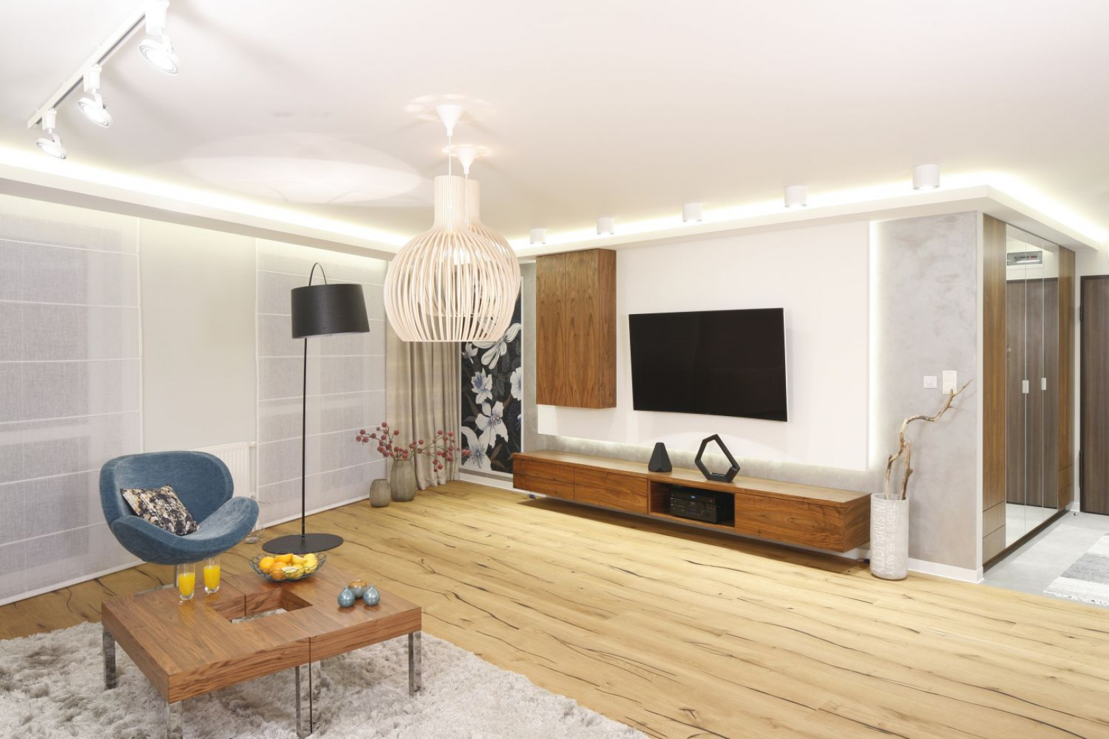 Przepiękna drewniana deska z mocno zaakcentowanymi sękami drewna zdobi podłogę w tym nowoczesnym salonie. Projekt: Agnieszka Hajdas-Obajtek. Fot. Bartosz Jarosz
