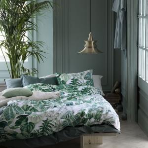 Komplet tekstyliów dekoracyjnych idealny zarówno do wnętrz, jak i na taras lub balkon. Utrzymany w kolorach zieleni i szarości. Fot. Broste Copenhagen