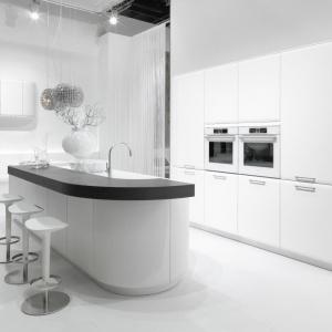 Model kuchni Onda w wersji białej ma opływowe kształty i kontrastujący ciemnobrązowy, niemal czarny blat, nakładany na wyspę. Fot. Rational