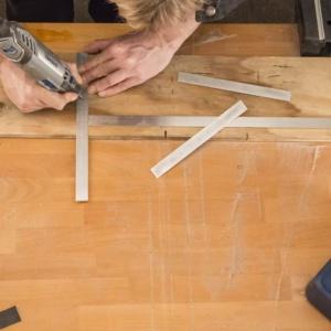 Krok 11: Utnij dwa kawałki płyty aluminiowej o długości 24 centymetrów używając narzędzia Dremel 4200 oraz tarczy tnącej do metalu. Następnie wygraweruj liczby w aluminium. Fot. Dremel