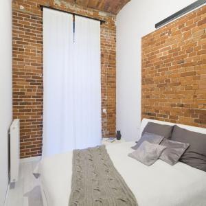 W sypialni na pierwszy plan wybijają się ceglane ściany. Na środku ustawiono białe łoże małżeńskie, nad którym zamontowano nowoczesny kinkiet. Projekt: Szymon Chudy. Fot. Bartosz Jarosz