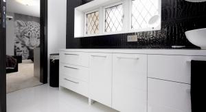 Biel i czerń to zawsze modna klasyka. W tej łazience czerń występuje na płytkach ceramicznych, które do złudzenia naśladują... skórę krokodyla.