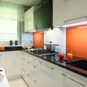 W tej wąskiej kuchni biała zabudowa na wysoki połysk odbija światło i duplikuje przestrzeń. Projekt: Studio Śląskie Kuchnie. Fot. Bartosz Jarosz