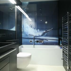 W czarno-białej łazience urządzonej w minimalistycznym stylu wzrok przyciąga dynamiczna fototapeta z pływającą kobietą. Projekt: Monika i Adam Bronikowscy