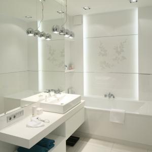 Skąpana w bieli nowoczesna łazienka. Nad wanną widnieje subtelny dekoracyjny wzór. Projekt: Anna Maria Sokołowska. Fot. Bartosz Jarosz