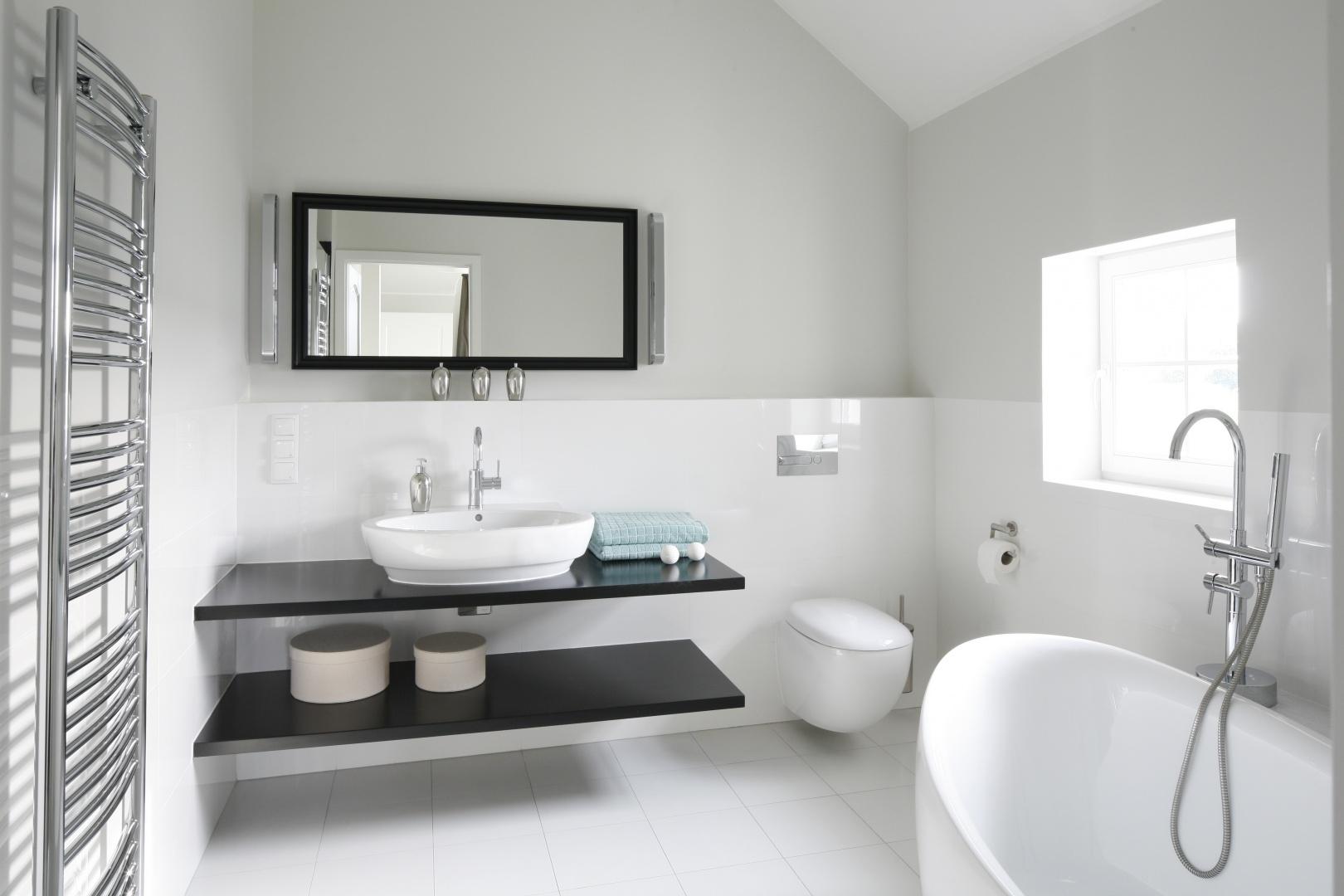 Biała łazienka urządzona w stylu, który jest mieszanką nowoczesności i klasyki. Dominację bieli przełamują delikatne czarne detale. Projekt: Ventana. Fot. Bartosz Jarosz