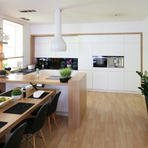 Białe matowe fronty zabudowy kuchennej ciekawie prezentują się oprawione w ramę w kolorze jasnego drewna, harmonizującą z blatem półwyspu kuchennego i podłogą w całej strefie dziennej. Projekt: Małgorzata Błaszczak. Fot. Bartosz Jarosz