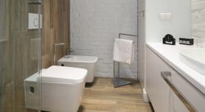Kolor drewna, biel, gładkość ceramiki oraz lakierowanych powierzchni – do tego surowość cegły. Aranżacja wnętrza stworzona na bazie materiałów o naturalnym wyglądzie jest elegancka i świeża.