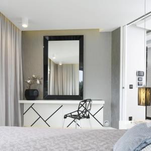 Sypialnia została wykończona niezwykle efektownie: pikowane obicie, lustro, a do tego dekoracyjna faktura ściany wokół tworzą luksusową aranżację. Projekt: Agnieszka Hajdas-Obajtek.
