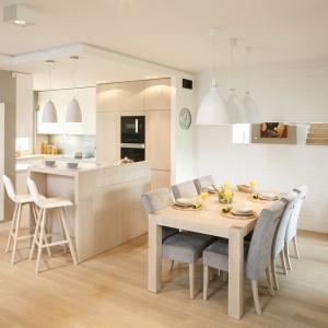 Jadalnia urządzona w sąsiedztwie otwartej kuchni: jasne drewno i szarości tworzą nowoczesne i efektowne zestawienie. Projekt: Małgorzata Galewska. Fot. Bartosz Jarosz