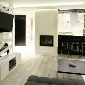 Telewizor umieszczony została na ażurowym panelu, który stanowi przepierzenie oddzielające jadalnię od salonu. Projekt: Dominik Respondek. Fot. Bartosz Jarosz