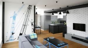 To wnętrze dla miłośników minimalizmu! Fototapeta na jednej ze ścian perfekcyjnie wkomponowuje się w wystrój całego wnętrza. Choć jest to przestrzeń urządzona bez zbędnych elementów, to posiada swój specyficzny klimat.