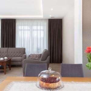 W salonie wykorzystano kamień naturalny oraz dekoracyjne tapety z subtelnym motywem geometrycznym.