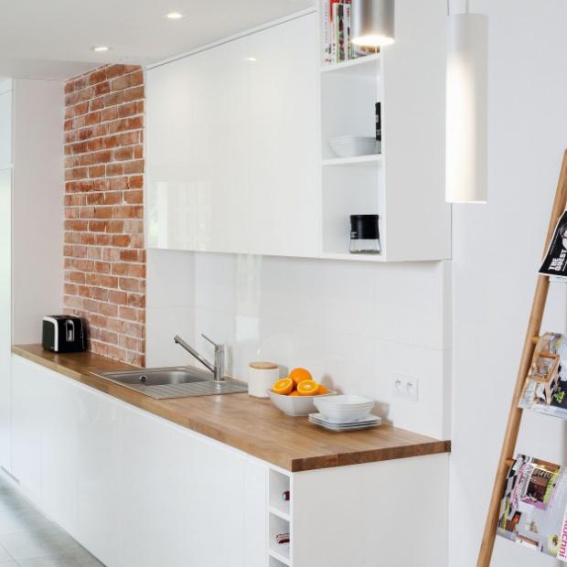 Projekt białej kuchni z drewnem i cegłą
