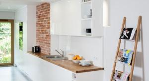 Loftowa kuchnia stylistycznie koresponduje z pozostałymi pomieszczeniami domu – połączono w niej ponadczasową biel oraz naturalny dąb. Klimatu dodają fragmenty ścian obłożone czerwoną cegłą, którą pani domu wyszukała na internetowej aukcj
