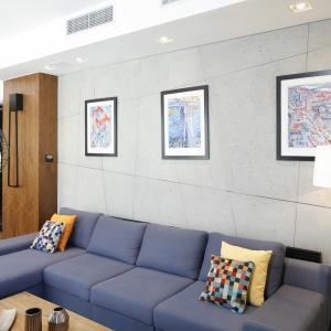 Ścianę w salonie wykończono betonem dekoracyjnym dodatkowy efekt dają zatopione aluminiowe listwy tworzące geometryczną siatkę. Fot. Bartosz Jarosz