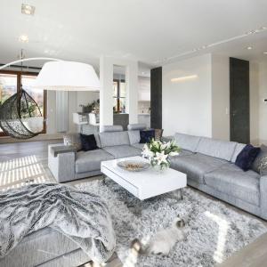 W pięknym nowoczesnym salonie podstawę aranżacji stanowią efektowne sofy w szarym kolorze. Projekt: Agnieszka Ludwinowska. Fot. Bartosz Jarosz