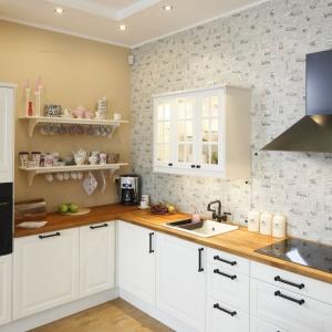 Utrzymany w rustykalnej manierze aneks kuchenny płynnie przechodzi w pokój dzienny, a jednorodność przestrzeni dodatkowo podkreśla jednolita posadzka na podłodze.