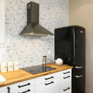 Tapeta z motywem gazetowego nadruku, którą wykończono ścianę nad kuchennym blatem sprawiła, że aneks nie ma typowo kuchennego charakteru.