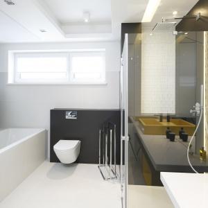 Łazienka, mimo minimalistycznych form wyposażenia, nie jest ani chłodna ani surowa. To zasługa kolorowych motyli tuż nad wanną oraz słonecznych akcentów na frontach mebli.