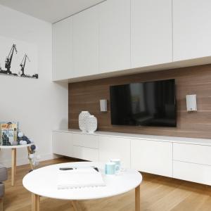 Na ścianie z telewizorem powstała nie tylko ciekawa, nowoczesna konstrukcja (białe szafki efektownie odcinają się na tle brązowej okładziny z forniru), ale także dodatkowa powierzchnia przechowywania, która w niewielkim mieszkaniu zawsze jest niezwykle cenna. Projekt: Przemek Kuśmierek. Fot. Bartosz Jarosz