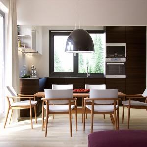 W kuchni dominację bieli przełamano czarną zabudową meblową. Z kolei, ulokowana obok kuchni spiżarka będzie idealnym miejscem do przechowywania. Fot. MTM Styl