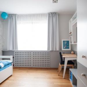 W sypialni dziecka również królują delikatne szarości, które stanowią piękną bazę dla kolorowych zabawek. Podwójną funkcję - do siedzenia i relaksu- w pokoju dziecięcym pełni niska półka na zabawki i książki. Fot. Adam Ościłowski