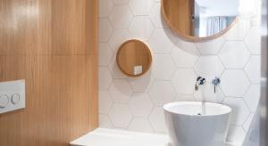 W aranżacji niewielkiej toalety projektanci postawili na dużą ilość bieli, ocieploną wizualnie słonecznym odcieniem drewna.