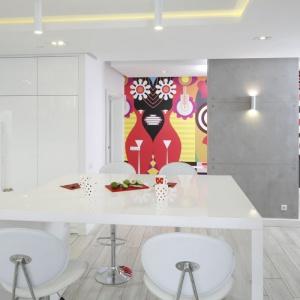 Po przeciwległej stronie kuchni i jadalni rozciąga się salon, w którym jedna ze ścian została wykończona betonem. Ta wąska ścianka ciekawie prezentuje się na tle barwnej ściany w holu. Proj. Dominik Respondek. Fot. Bartosz Jarosz