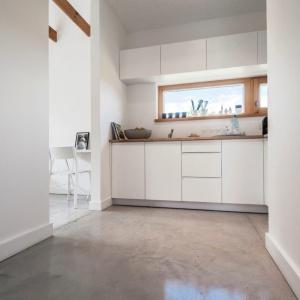 Na całości parteru konstancińskiego domu została wykorzystana cienkowarstwowa posadzka Baufloor Ultima® w kolorze ULT603. Jasna, świetlista szarość o ciepłym odcieniu bardzo dobrze komponuje się z białym wnętrzem, stolarką i meblami. Fot. Bautech Futura