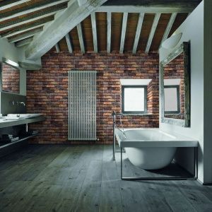 Odkryta więźba dachowa i cegła to centralne punkty wystroju nowoczesnej łazienki. Fot. CRH Klinkier