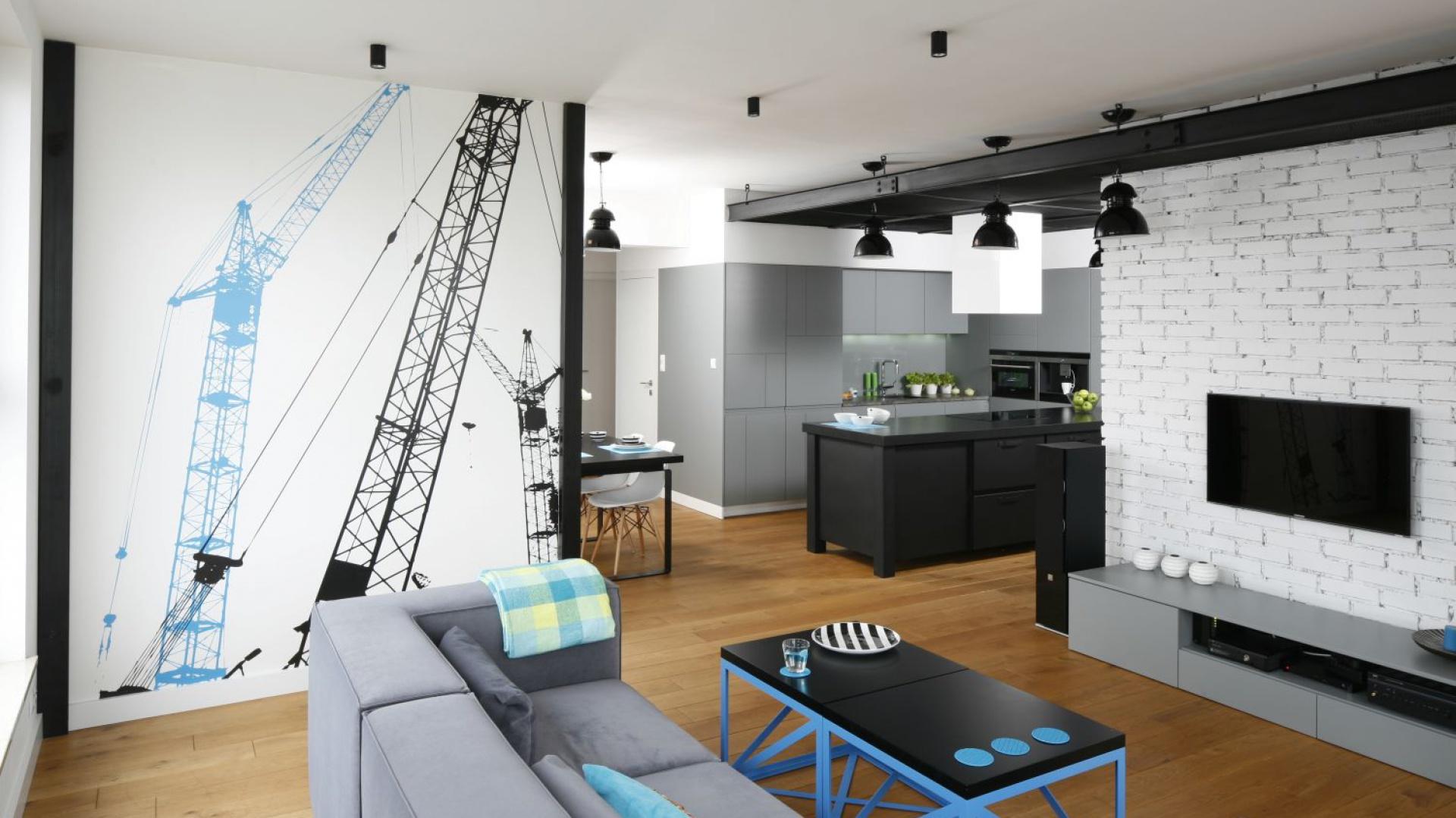 Wnętrze w minimalistycznym, nieco loftowym stylu zdobi cegła na jednej ze ścian. Pięknie komponuje się z fototapetą i czarnymi elementami sufitu podwieszanego. Projekt: Monika i Adam Bronikowscy. Fot. Bartosz Jarosz