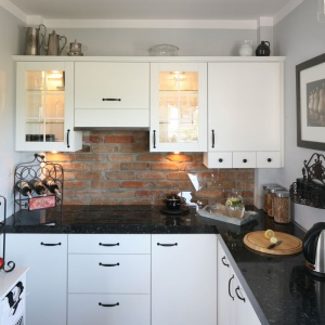Biała zabudowa kuchenna pięknie prezentuje się na tle czerwonych, ręcznie formowanych cegieł. Projekt: Magdalena Kwiatkowska. Fot. Bartosz Jarosz