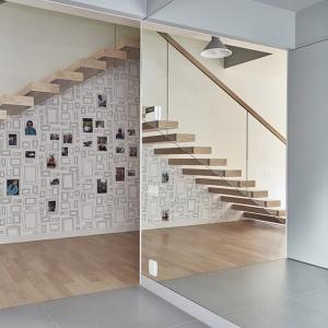 Pod schodami powstało miejsce przeznaczone na domową galerię, w której można wklejać rodzinne fotografie. Fot. 81.waw.pl