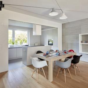 Z całym wnętrzem współgrają również meble. Główną rolę odgrywa duży drewniany stół oraz szaro-czarne krzesła, z których wyróżnia się jedno czerwone. Fot. 81.waw.pl