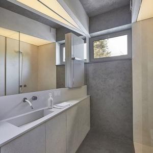 Skos, który powstał w łazience, wynika z rozmieszczenia drzwi i okienka, które nie znajdują się w linii prostej. Dzięki temu przestrzeń w łazience została wyrównana. Oświetlenie stanowią napinane świecące sufity Barissol. Fot. 81.waw.pl