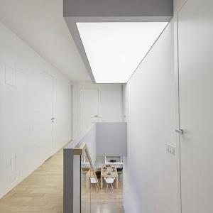 W holu na piętrze posadzka jest drewniana i znajduje się na niej pełna balustrada. Oświetlenie to wiszący sufit, który podkreśla trzon schodów. Zgodnie z całą koncepcją projektu, ściany są białe z geometrycznym wzorem, który został zastosowany także na parterze. Fot. 81.waw.pl
