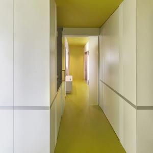 W łazience głównej, która znajduje się przy sypialni, również użyto linoleum, ale oliwkowego. Zamysł pozostał jednak ten sam - ciąg komunikacyjny jest podkreślony jednym kolorem. Podobnie jak w całym domu, ściany pozostały białe, a wnęki szare. Fot. 81.waw.pl
