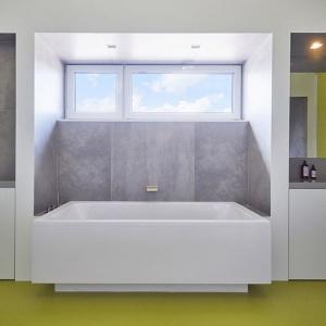 Zamkniętą przestrzeń stanowi jedynie łazienka gościnna, która w całości została pokryta mikrobetonem. Pojawia się również na szafkach i w prysznicu, ponieważ jest wodoodporny. Ciemny pas podkreśla strefę komunikacji, czyli wejście, sufit i okienko. Fot. 81.waw.pl