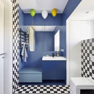Łazienka dziecięca to najbardziej kolorowe wnętrze domu. Komunikacja została podkreślona biało-czarną glazurą, jak w szachownicy, a umywalka i wanna są niebieskie. Zostały wyłożone wodoodporną wykładziną – linoleum.  Dziecięcym akcentem, dodatkowo rozweselającym wnętrze, jest oświetlenie przy suficie, które ma kształt kolorowych balonów. Fot. 81.waw.pl